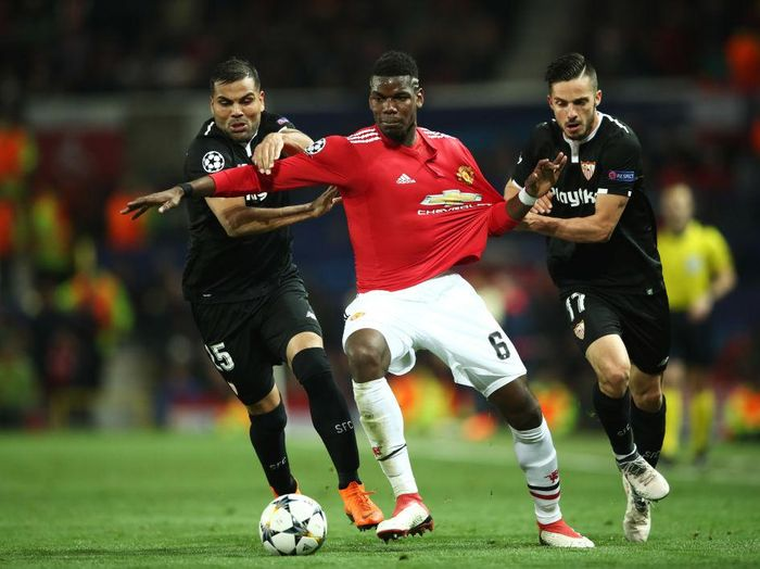 MANCHESTER, ENGLAND - MARCH 13:  Paul Pogba of Manchester United battles with Gabriel Mercado and Pablo Sarabia of Sevilla during the UEFA Champions League Round of 16 Second Leg match between Manchester United and Sevilla FC at Old Trafford on March 13, 2018 in Manchester, United Kingdom.  (Photo by Clive Mason/Getty Images)