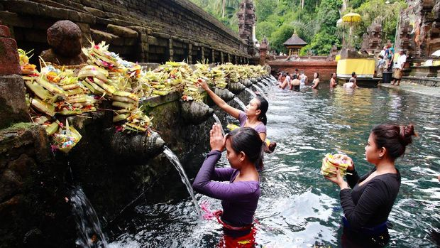 Bali, Indonesia - May 6, 2013: Worshippers make an offering at the Tirta Empul Temple in Bali, Indonesia.