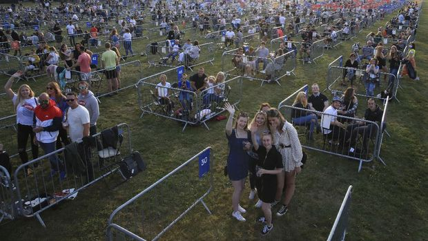 Fans occupy separate pens to force social distancing, ahead of the Sam Fender rock concert at the Virgin Money Unity Arena, a pop-up venue for the gig in Gosforth Park, Newcastle, northern England, Tuesday Aug. 11, 2020.  Fans in groups of up to five people will watch the show from 500 separated zones at what the promoters say is the world's first socially-distanced COVID-19 gig. (Owen Humphreys/PA via AP)
