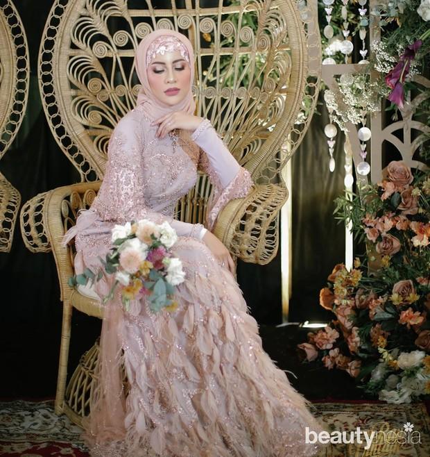 Dengan taburan swarovski di seluruh permukaan gaun membuat Fira tampil mewah