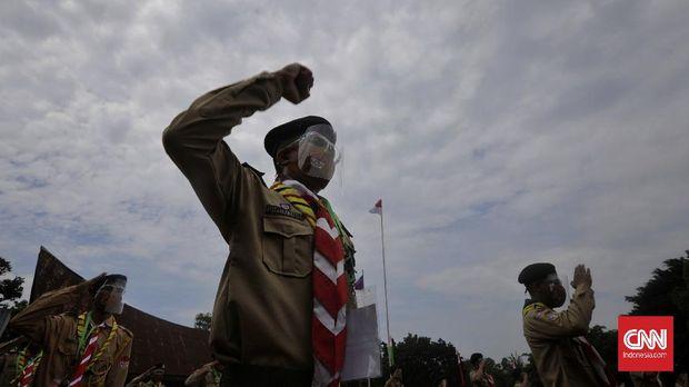 Sejumlah peserta berlatih memanjat pohon dengan tali dalam perkemahan Hari Pramuka di Bumi Perkemahan Pramuka, Cibubur, Jakarta, Jumat (14/8/2020). Perkemahan yang digelar Saka Wira Kartika TNI AD tersebut diikuti 500 anggota Pramuka se-Jabodetabek dan dilakukan dengan menerapkan protokol kesehatan selama pandemi COVID-19, seperti penggunaan masker, pelindung wajah, dan penerapan satu tenda satu orang.  (CNN Indonesia/ Adhi Wicaksono)