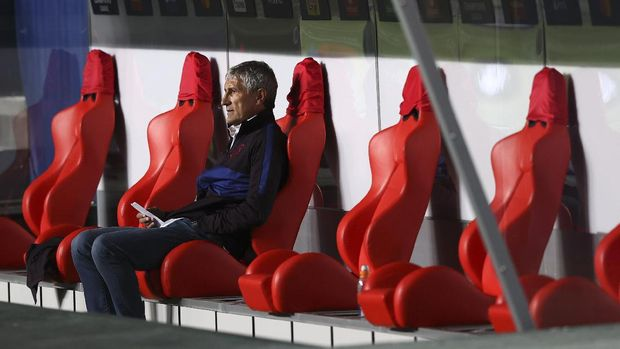 Barcelona's head coach Quique Setien sits on the bench before the start of the second half of the Champions League quarterfinal soccer match between Barcelona and Bayern Munich in Lisbon, Portugal, Friday, Aug. 14, 2020. (Rafael Marchante/Pool via AP)