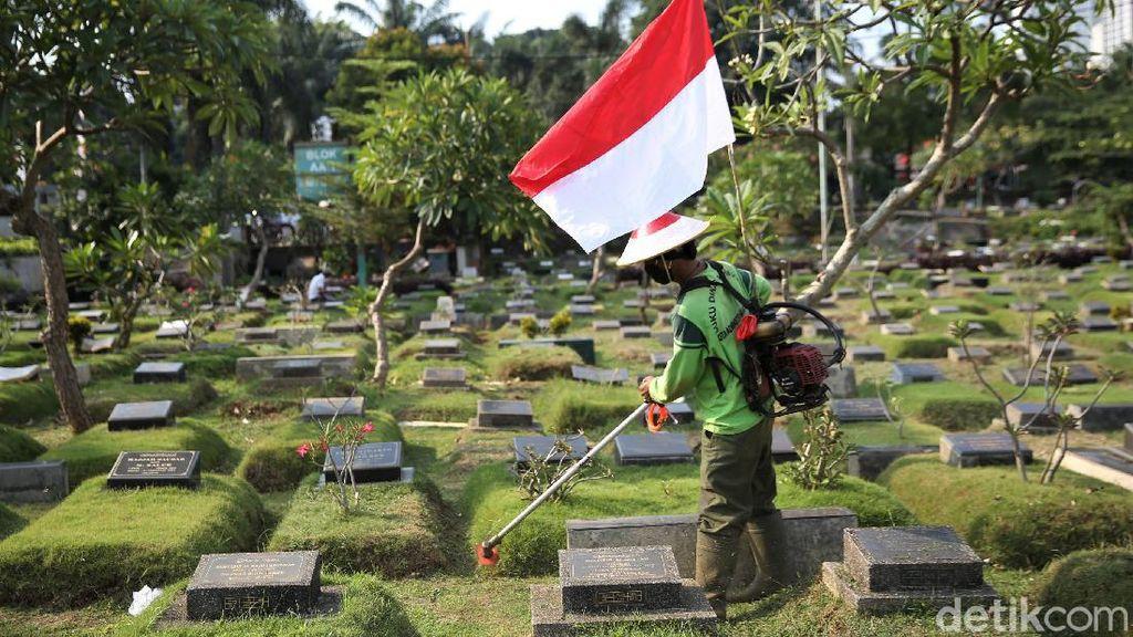 Aksi Petugas Bersihkan TPU Karet Bivak Sambil Bawa Bendera