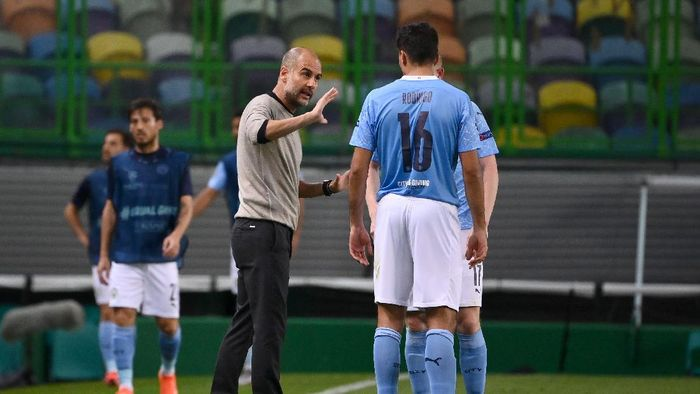 LISBON, PORTUGAL - AUGUST 15: Pep Guardiola, Manager of Manchester City speaks with Rodrigo of Manchester City during the UEFA Champions League Quarter Final match between Manchester City and Lyon at Estadio Jose Alvalade on August 15, 2020 in Lisbon, Portugal. (Photo by Franck Fife/Pool via Getty Images)