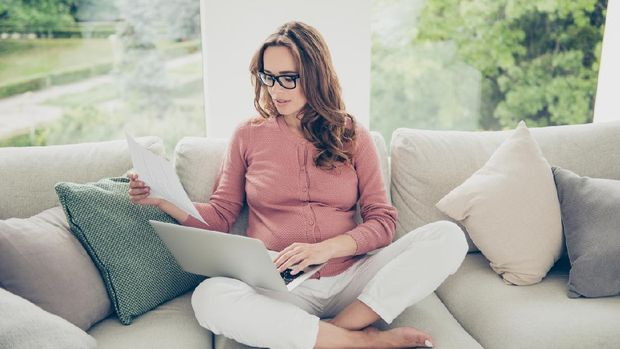Above high angle view of nice lovely beautiful minded serious pregnant curly-haired mom in casual wear sitting on sofa, couch, divan, working remotely, lotus pose, white light interior room