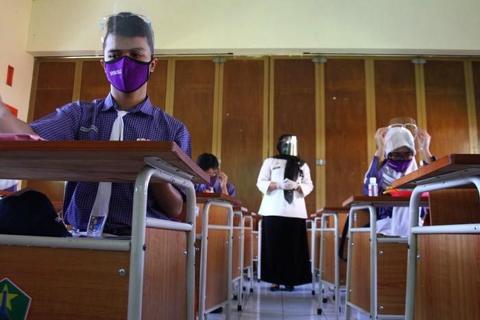 Petugas Usaha Kesehatan Sekolah (UKS) yang mengenakan Alat Pelindung Diri (APD) memperagakan cara merawat pelajar yang sakit saat Simulasi Pembelajaran Sekolah Dengan Protokol Kesehatan di SMPN 8 Malang, Jawa Timur, Rabu (19/8/2020). Simulasi tersebut diadakan untuk melatih para siswa dan guru dalam penerapan protokol kesehatan di lingkungan sekolah guna mencegah penyebaran COVID-19. ANTARA FOTO/Ari Bowo Sucipto/aww.