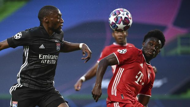 Lyon's Karl Toko Ekambi, left, duels for the ball with Bayern's Alphonso Davies during the Champions League semifinal soccer match between Lyon and Bayern at the Jose Alvalade stadium in Lisbon, Portugal, Wednesday, Aug. 19, 2020. (Franck Fife/Pool via AP)
