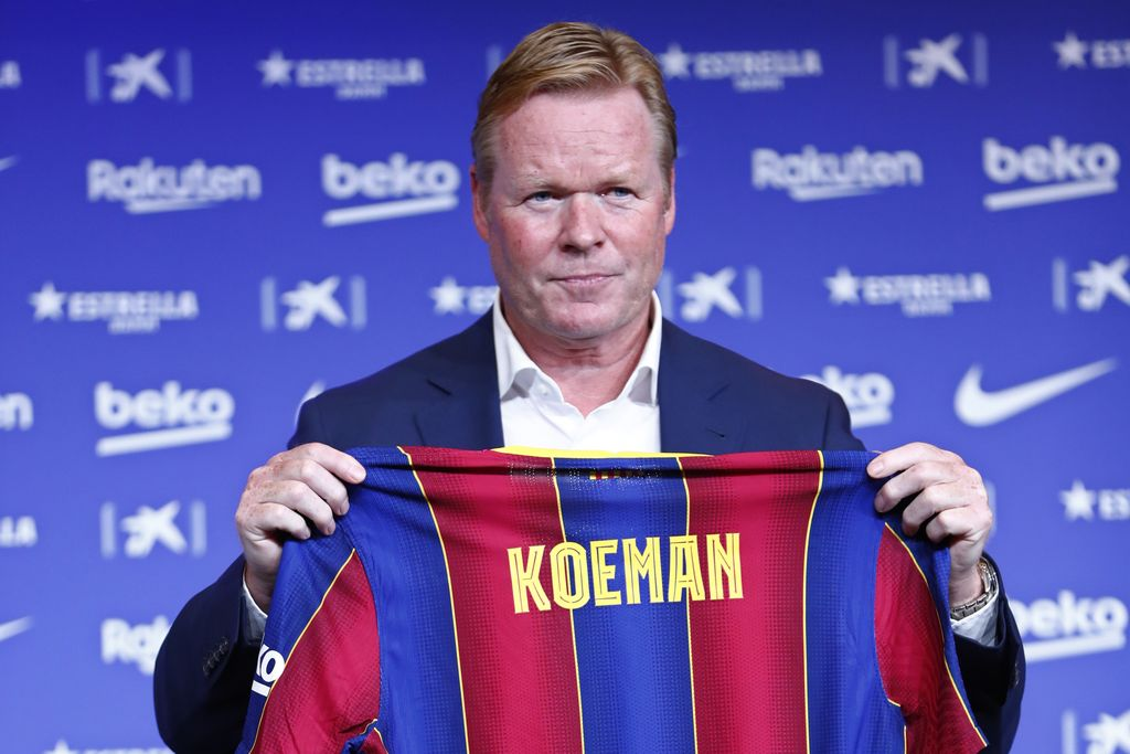 Ronald Koeman holds up a soccer shirt with his name on it during his official presentation as coach for FC Barcelona in Barcelona, Spain, Wednesday, Aug. 19, 2020. Barcelona officially announced earlier on Wednesday a deal with Koeman to become their coach five days after the team's humiliating 8-2 loss to Bayern Munich in the Champions League quarterfinals. Barcelona says the former defender's deal runs through June 2022. Koeman replaces the fired Quique Setien. (AP Photo/Joan Monfort)