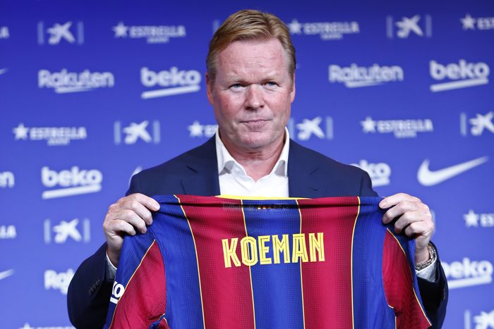 Ronald Koeman holds up a soccer shirt with his name on it during his official presentation as coach for FC Barcelona in Barcelona, Spain, Wednesday, Aug. 19, 2020. Barcelona officially announced earlier on Wednesday a deal with Koeman to become their coach five days after the teams humiliating 8-2 loss to Bayern Munich in the Champions League quarterfinals. Barcelona says the former defenders deal runs through June 2022. Koeman replaces the fired Quique Setien. (AP Photo/Joan Monfort)