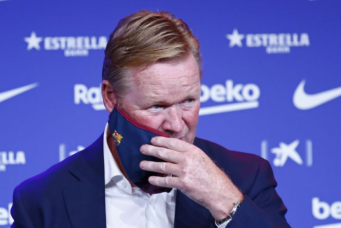 Ronald Koeman takes of his protective face mask during his official presentation as coach for FC Barcelona in Barcelona, Spain, Wednesday, Aug. 19, 2020. Barcelona officially announced earlier on Wednesday a deal with Koeman to become their coach five days after the teams humiliating 8-2 loss to Bayern Munich in the Champions League quarterfinals. Barcelona says the former defenders deal runs through June 2022. Koeman replaces the fired Quique Setien. (AP Photo/Joan Monfort)