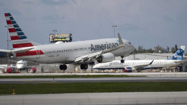 FORT LAUDERDALE, FLORIDA - JULY 16: An American Airlines plane lands on a runway near a parked JetBlue plane at the Fort Lauderdale-Hollywood International Airport on July 16, 2020 in Fort Lauderdale, Florida. JetBlue Airways and American Airlines Group announced they will be creating an alliance between the two companies.   Joe Raedle/Getty Images/AFP