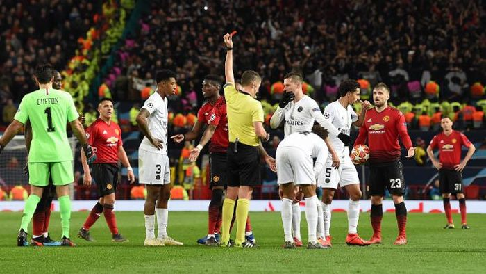 Italian referee Daniele Orsato (C) shows a red card to to Manchester Uniteds French midfielder Paul Pogba (centre L) during the first leg of the UEFA Champions League round of 16 football match between Manchester United and Paris Saint-Germain (PSG) at Old Trafford in Manchester, north-west England on February 12, 2019. (Photo by Paul ELLIS / AFP)