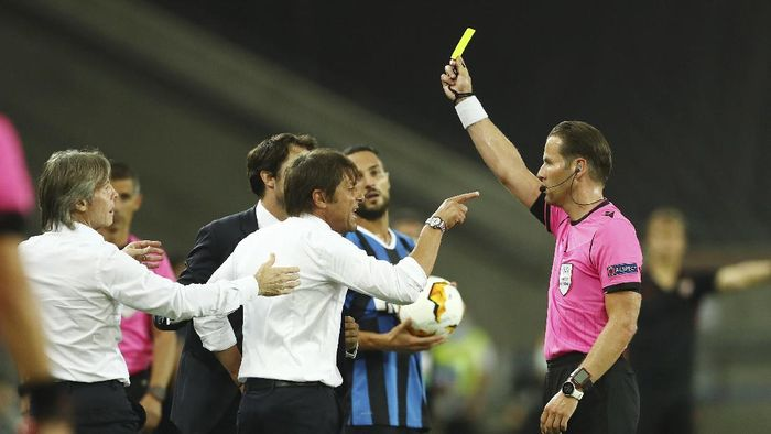 Referee Danny Makkelie gives a yellow card to Inter Milans head coach Antonio Conte during the Europa League final soccer match between Sevilla and Inter Milan in Cologne, Germany, Friday, Aug. 21, 2020. (Lars Baron, Pool Photo via AP)