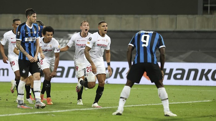 Sevillas Diego Carlos, second from right, celebrates after scoring his sides third goal as Inter Milans Romelu Lukaku, right, reacts during the Europa League final soccer match between Sevilla and Inter Milan in Cologne, Germany, Friday, Aug. 21, 2020. (Lars Baron, Pool Photo via AP)