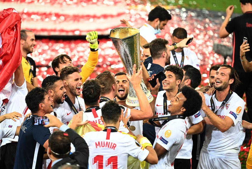 COLOGNE, GERMANY - AUGUST 21: Luuk de Jong, Joan Jordan, Jose Mena, Jules Kounde of Sevilla, and their teammates celebrate with the UEFA Europa League Trophy following their team's victory in the UEFA Europa League Final between Seville and FC Internazionale at RheinEnergieStadion on August 21, 2020 in Cologne, Germany. (Photo by Lars Baron/Getty Images)