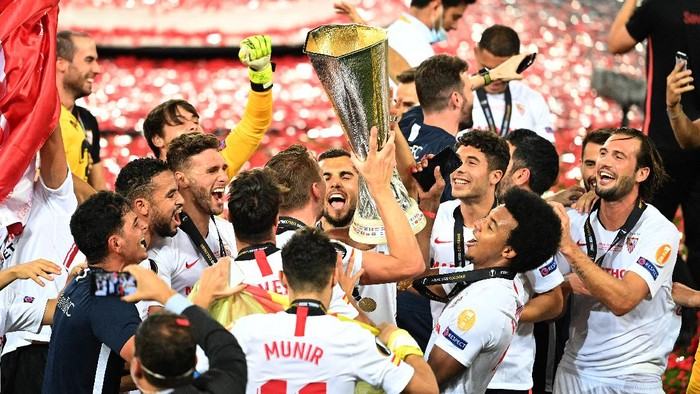 COLOGNE, GERMANY - AUGUST 21: Luuk de Jong, Joan Jordan, Jose Mena, Jules Kounde of Sevilla, and their teammates celebrate with the UEFA Europa League Trophy following their teams victory in the UEFA Europa League Final between Seville and FC Internazionale at RheinEnergieStadion on August 21, 2020 in Cologne, Germany. (Photo by Lars Baron/Getty Images)