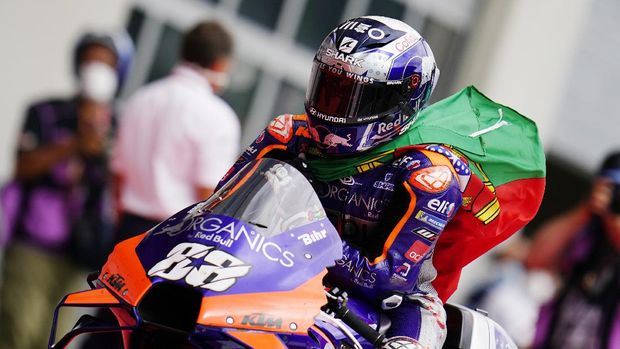 Portugal's KTM driver Miguel Oliveira carries a flag after winning the MotoGP race at the Austrian motorcycle Grand Prix at the Red Bull Ring in Spielberg, Austria, Sunday, Aug. 23, 2020. (AP Photo/Steve Wobser)