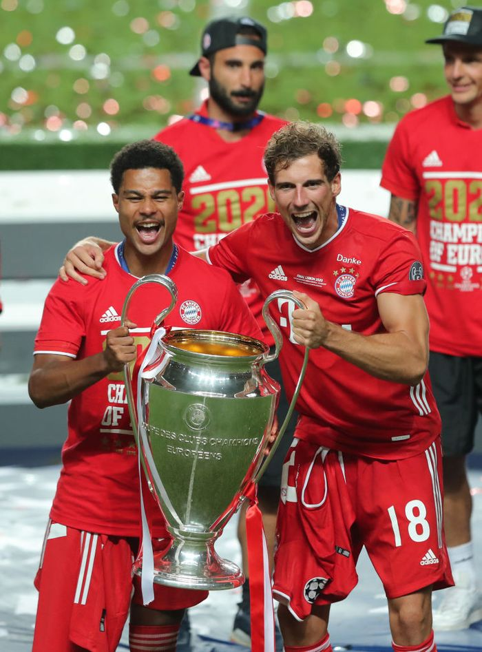 LISBON, PORTUGAL - AUGUST 23: Serge Gnabry of FC Bayern Munich and team mate Leon Goretzka celebrate with the Champions League Trophy following their teams victory in the UEFA Champions League Final match between Paris Saint-Germain and Bayern Munich at Estadio do Sport Lisboa e Benfica on August 23, 2020 in Lisbon, Portugal. (Photo by Miguel A. Lopes/Pool via Getty Images)