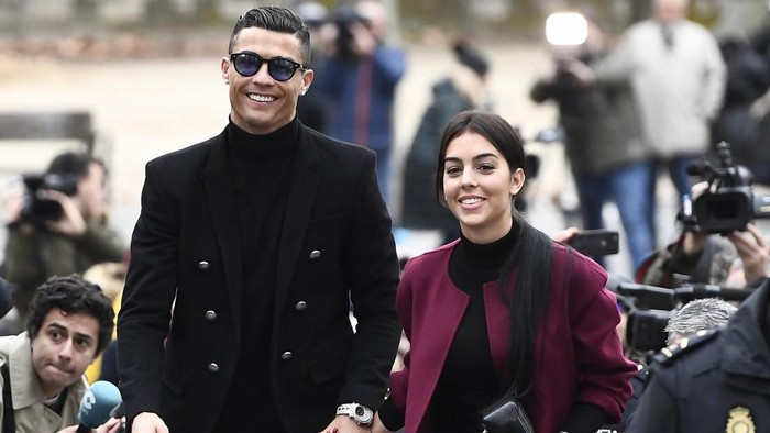 Juventus forward and former Real Madrid player Cristiano Ronaldo arrives with his Spanish girlfriend Georgina Rodriguez to attend a court hearing for tax evasion in Madrid on January 22, 2019. - Ronaldo is expected to be given a hefty fine after Spanish tax authorities and the players advisors made a deal to settle claims he hid income generated from image rights when he played for Real Madrid. (Photo by PIERRE-PHILIPPE MARCOU / AFP)