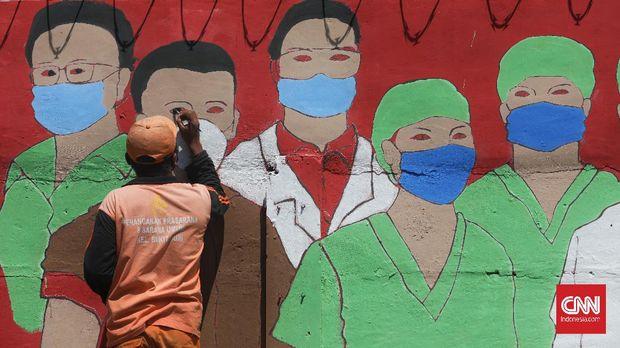Petugas PPSU Bukit Duri menyelesaikan pembuatan mural yang berisi pesan waspada penyebaran virus Corona di kawasan Bukit Duri, Jakarta, Kamis, 27 Agustus 2020. Pelaksanaan pembatasan sosial berskala besar (PSBB) transisi di DKI Jakarta sejak 14 Agustus 2020 akan berakhir Kamis (27/8). CNN Indonesia/Safir Makki