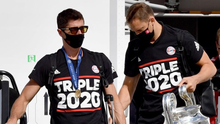 MUNICH, GERMANY - AUGUST 24: Robert Lewandowski (L) and Manuel Neuer of FC Bayern Muenchen disembark the airplane with the trophy as UEFA Champions League winners FC Bayern Munich arrive at Airport Munich on August 24, 2020 in Munich, Germany. (Photo by Philipp Guelland - Pool/Getty Images)