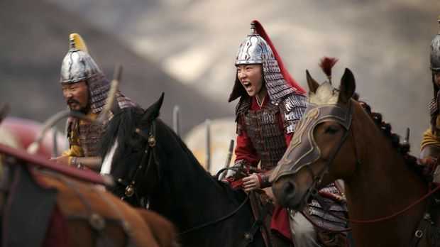 This image released by Disney shows Yifei Liu, center, in the title role of