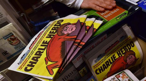 The first issues of the German version of French satirical weekly Charlie Hebdo are for sale at a newsstand in Berlin on December 1, 2016. (Photo by John MACDOUGALL / AFP)