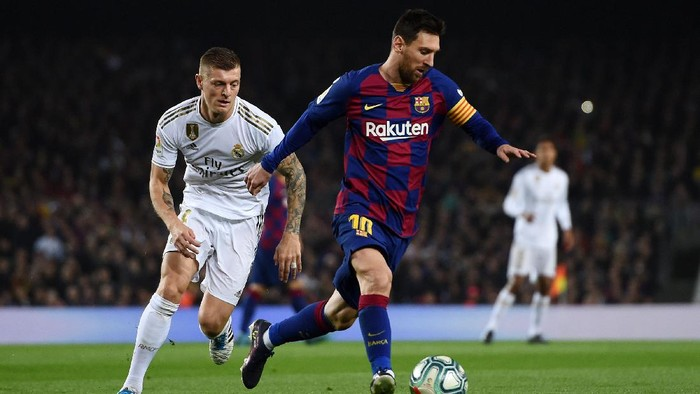 BARCELONA, SPAIN - DECEMBER 18:  Lionel Messi of Barcelona holds off Toni Kroos of Real Madrid during the Liga match between FC Barcelona and Real Madrid CF at Camp Nou on December 18, 2019 in Barcelona, Spain. (Photo by Alex Caparros/Getty Images)