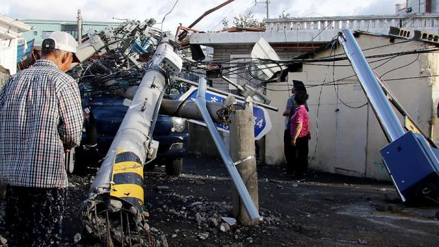People look at an electric pole downed by Typhoon Maysak in the southeastern port city of Ulsan on September 3, 2020. - At least one person was killed and more than 2,000 people evacuated to temporary shelters in South Korea as a powerful typhoon churned across the peninsula, authorities said on September 3. (Photo by - / YONHAP / AFP) / - South Korea OUT / REPUBLIC OF KOREA OUT  NO ARCHIVES  RESTRICTED TO SUBSCRIPTION USE