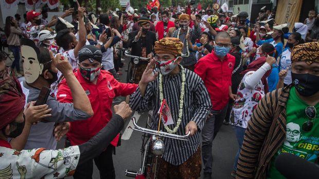 Pasangan bakal calon Wali Kota dan Wakil Wali Kota Solo Gibran Rakabuming Raka (kelima kiri) dan Teguh Prakosa (kelima kanan) menaiki sepeda ontel menuju kantor KPU Solo untuk melakukan pendaftaran Pemilihan Wali Kota (Pilwakot) 2020 di Solo, Jawa Tengah, Jumat (4/9/2020). Gibran Rakabuming Raka dan Teguh Prakosa yang diusung PDI Perjuangan resmi mendaftarkan diri ke KPU Kota Solo sebagai pasangan bakal calon Wali Kota dan Wakil Wali Kota pada Pilkada 2020 mendatang. ANTARA FOTO/Mohammad Ayudha/wsj.