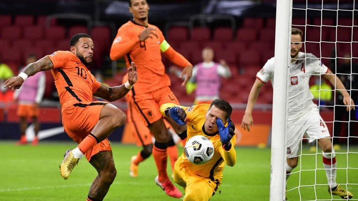 Polands goal keeper Bartlomiej Dragowski (R) stops the ball in front of Dutchs forward Memphis Depay (L) during the UEFA Nations League football match between Netherlands and Poland at the Johan Cruijff Arena stadium, in Amsterdam, on September 4, 2020. (Photo by JOHN THYS / AFP)