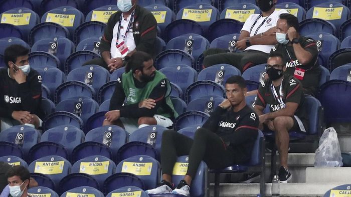 Portugals Cristiano Ronaldo, foreground right, watches form the stands the UEFA Nations League soccer match between Portugal and Croatia at the Dragao stadium in Porto, Portugal, Saturday, Sept. 5, 2020. Ronaldo is not playing due to an injury. (AP Photo/Miguel Angelo Pereira)