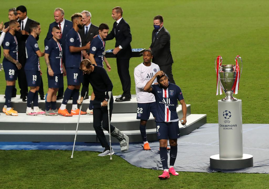 LISBON, PORTUGAL - AUGUST 23: Kylian Mbappe of Paris Saint-Germain removes his runners up medal as he walks past the UEFA Champions League Trophy following his team's defeat in the UEFA Champions League Final match between Paris Saint-Germain and Bayern Munich at Estadio do Sport Lisboa e Benfica on August 23, 2020 in Lisbon, Portugal. (Photo by Miguel A. Lopes/Pool via Getty Images)