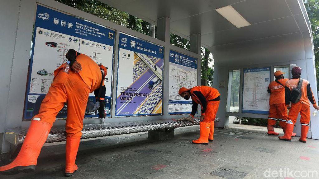 Aksi Pasukan Oranye Bersihkan Halte Bus di Jalan Sudirman