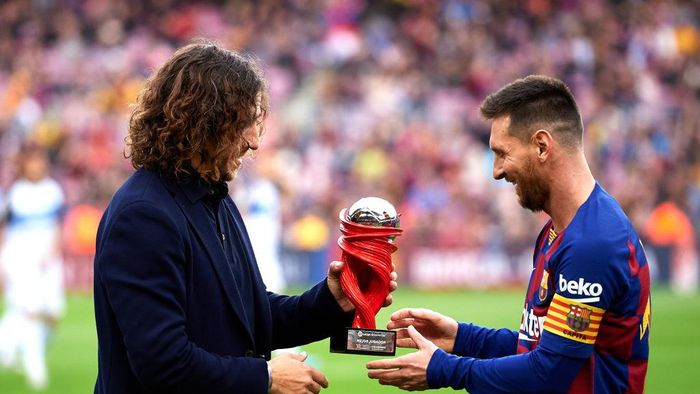 BARCELONA, SPAIN - DECEMBER 21: Lionel Messi of FC Barcelona receives the trophy as best player of November in the Spanish La Liga from Carles Puyol  before the La Liga match between FC Barcelona and Deportivo Alaves at Camp Nou on December 21, 2019 in Barcelona, Spain. (Photo by Alex Caparros/Getty Images)