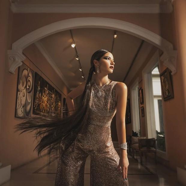 Dalam pemotretan bersama fotografer Rio Motret, Nia Ramadhani mengenakan jumpsuit dengan bahan glittery berwarna cokelat keemasan dari desainer Ivan Gunawan.