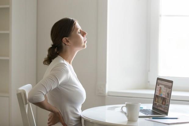 Saat kamu duduk tapi posisi agak membungkuk, otot dan ligamen di punggung bisa tegang