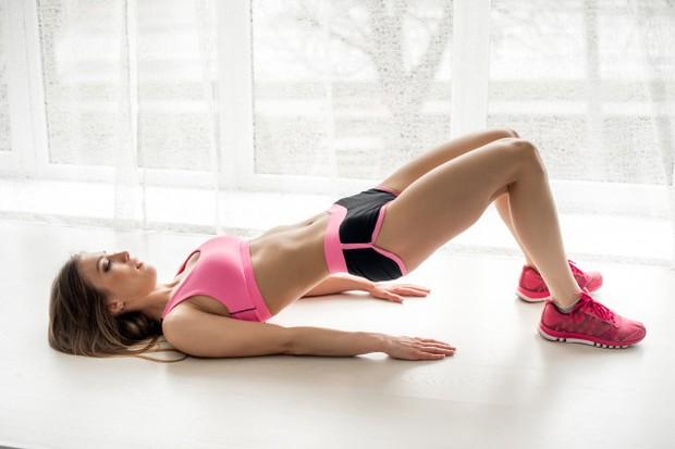 seorang wanita melakukan peregangan untuk meredakan nyeri punggung bawah