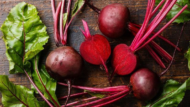 Red Beetroot with herbage green leaves on wooden background