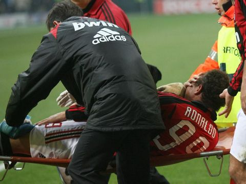 A.C. Milan's Brazilian forward Ronaldo holds his face while is carried out  during  their