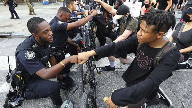 FILE - Atlanta police officer J. Coleman, left, and protester Elijah Raffington fist bump while officers kneel down with protesters in a symbolic gesture of solidarity outside the CNN Center, Wednesday, June 3, 2020, in Atlanta during a protest sparked by the May 25 death of George Floyd in Minneapolis police custody.