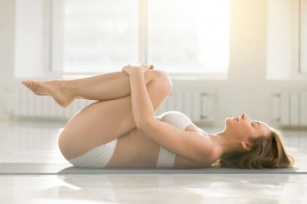 Seorang wanita sedang melakukan peregangan Knee-to-Chest Stretch