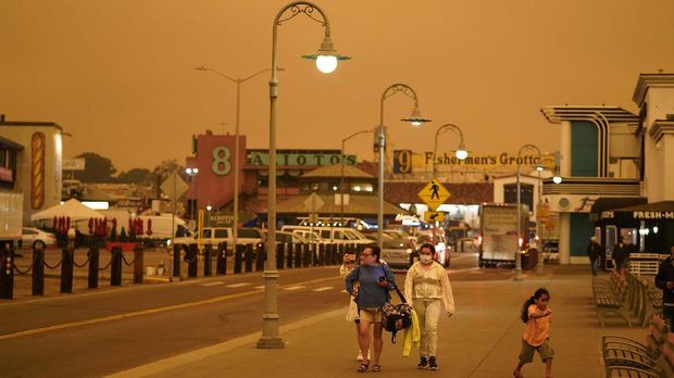 Under darkened skies from wildfire smoke, people walk at Fisherman's Wharf Wednesday, Sept. 9, 2020, in San Francisco. People from San Francisco to Seattle woke Wednesday to hazy clouds of smoke lingering in the air, darkening the sky to an eerie orange glow that kept street lights illuminated into midday, all thanks to dozens of wildfires throughout the West. The picture was taken in the middle of the day at 1:01 p.m. (AP Photo/Eric Risberg)