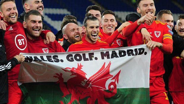 Gareth Bale membentangkan bendera Wales dengan bertuliskan 'Wales. Golf. Madrid. In That Order'.