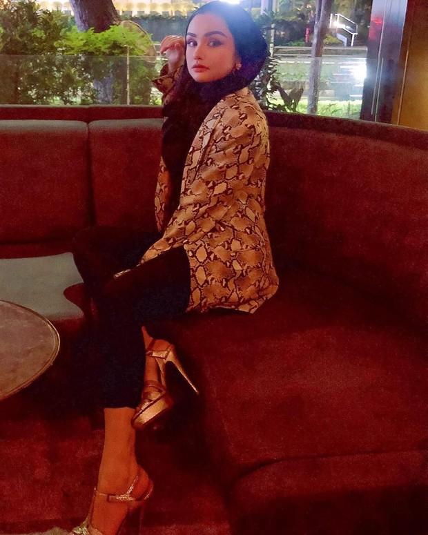 Gaya berkelas Nourah ketika mengenakan outer dengan motif snake skin bersamaan dengan strap heels berwarna senada