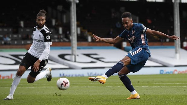 Arsenal's Pierre-Emerick Aubameyang, right, kicks the ball during the English Premier League soccer match between Fulham and Arsenal in London, Saturday, Sept. 12, 2020. (Paul Childs/Pool via AP)