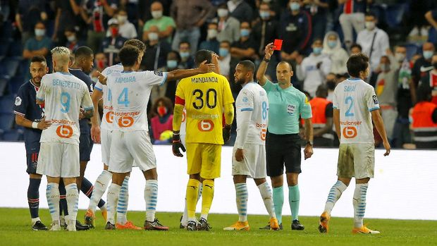 Referee Jerome Brisard gives a red card, one of 5 he awarded during the French League One soccer match between Paris Saint-Germain and Marseille at the Parc des Princes in Paris, France, Sunday, Sept.13, 2020. (AP Photo/Michel Euler)