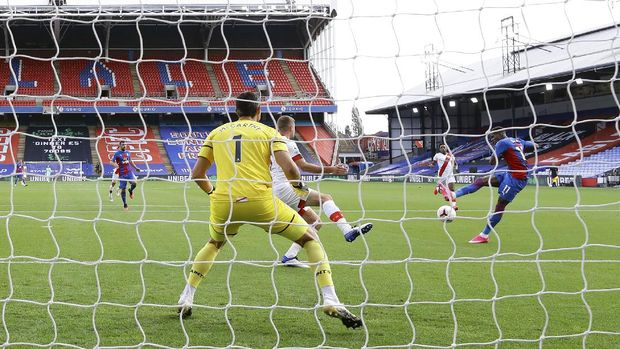 Crystal Palace's Wilfried Zaha, right, scores his side's opening goal during the English Premier League soccer match between Crystal Palace and Southampton, at Selhurst Park, London, Saturday, Sept. 12, 2020. (Richard Heathcote, Pool via AP)