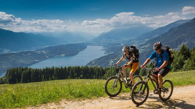 A couple is biking uphill on a scenic forest road with an overview of Lake Millstatt, Carinthia, southern Austria. The region is a very attractive holiday area and is famous for hiking, mountainbiking and swimming during summertime. In wintertime there lots of skiing areas as well.