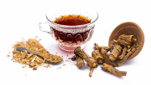Dried Indian sarsaparilla or Hemidesmus indicus or nannari or annatmol with its syrup and powder used in mant Indian & Asian beverages isolated on white.